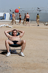 Three  British soldiers  serving with the Muliti National Division one in civilian clothes spends time relaxing, sun bathing and playing volleyball, while off duty at Basra Air Station during Op Telic Iraq 2005