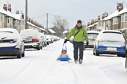Licensed to London News Pictures 28/01/2018<br /> A man pulls his daughter on a sledge down the centre of street in snow bound Harrogate, North Yorkshire<br /> Photo Credit: Sam Atkins/LNP