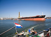 Spido boat trip on the River Maas through the Port of Rotterdam, Netherlands passing the 'Panamax Giant' cargo ship.