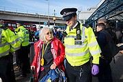 An elderly woman is arrested as climate change protest group Extinction Rebellion stage a protest at London City Airport during day four of two weeks of planned demonstrations on 10th October, 2019 in London, Untited Kingdom. Extinction Rebellion is demanding that governments drastically cut carbon emissions.