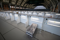 © Licensed to London News Pictures. 10/04/2020. Manchester, UK. A single bed has been placed in a bay in the hospital . The National Health Service is building a 648 bed field hospital for the treatment of Covid-19 patients , at the historical railway station terminus which now forms the main hall of the Manchester Central Convention Centre . The facility is due to open next week and will treat patients from across the North West of England , providing them with general medical care and oxygen therapy after discharge from Intensive Care Units . Photo credit: Joel Goodman/LNP