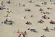 Nederland, Nijmegen, 1-8-2020 Een warme dag in de zomer . Mensen trekken naar de oevers van de waal en de spiegelwaal in het rivierpark aan de overkant van Nijmegen . De warmte, hoge temperatuur, drijft mensen naar het water . Het is verboden in de rivier te zwemmen vanwege de stroming en het drukke scheepvaartverkeer . . Vanwege de coronadreiging moet afstand gehouden worden, maar vooral jongeren, jonge mensen, zitten soms in groepen bij elkaar . Foto: ANP/ Hollandse Hoogte/ Flip Franssen