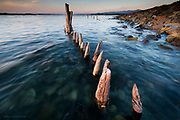 I took this photograph whilst being filmed for a new ITV series 'The Strait' <br /> <br /> The cameraman and I were being bitten senseless by a million midgies as we waited for the tide to rise over these heavily weathered wooden posts. Normally I would have gone exploring whilst waiting for right height for the sea, but the hassle of setting up filming positions meant that perhaps this half an hour was the longest I've ever waited for a photograph. <br /> <br /> The strong earlier sunshine had weakened behind a soft bank of cloud, removing the high contrast I wanted. However the gentleness of the light has still worked nicely for me nevertheless. Indeed, there is something more calming and serene about the light and colours in this image than originally anticipated.