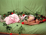 Young child of 7 lying down covered with red roses