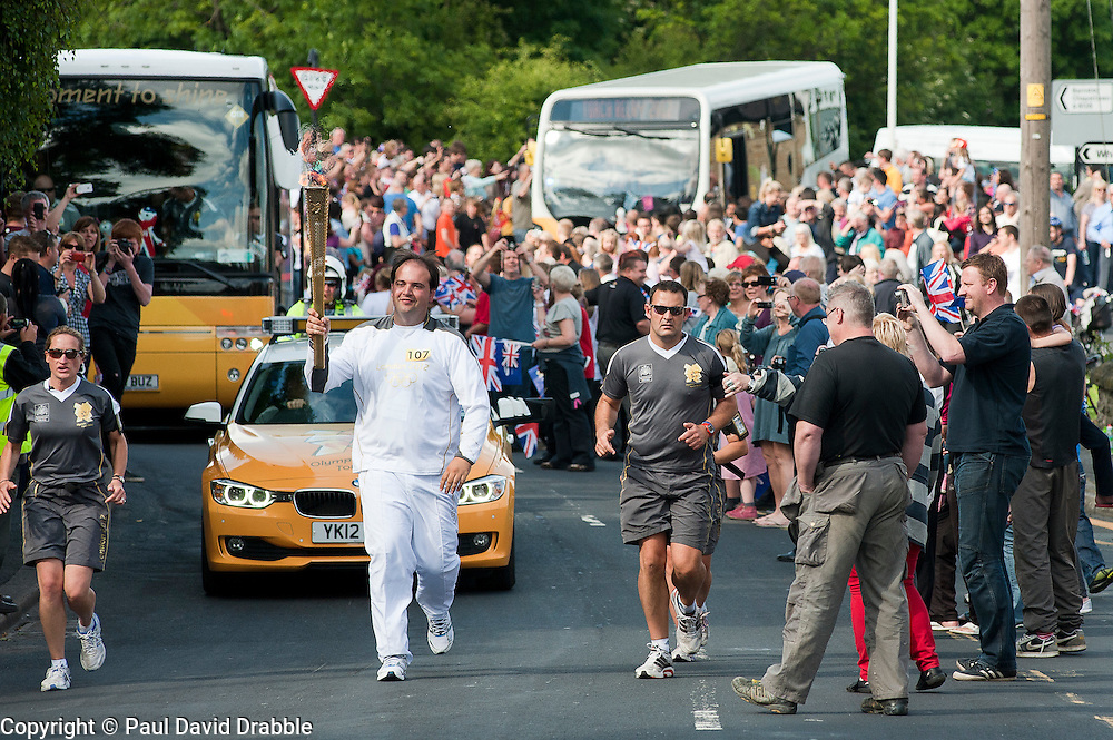 The Olympic Torch relay reaches Sheffield on day 38 coverage from the Chapeltown - Ecclesfield - Parson Cross section of the Journey.<br /> Runner 107 Irigoyen Angulo takes his turn carrying the Olympic flame up Church street in Ecclesfield<br /> 25 June 2012.Image © Paul David Drabble