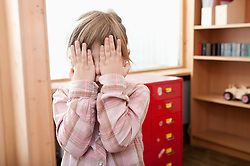 Little girl covering her face with her hands