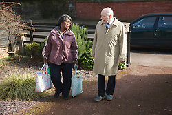 Carer carrying shopping for pensioner.