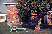 Retro America - 1970's life. Chase lounge and American flag in suburban back yard. Brick ,NJ