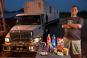 """Tersius """"Teri"""" Bezuidenhout, a long-haul trucker delayed by paperwork at the Botswana-Namibia border stands next to his truck with his typical day's worth of road food. (From the book What I Eat: Around the World in 80 Diets.) MODEL RELEASED."""