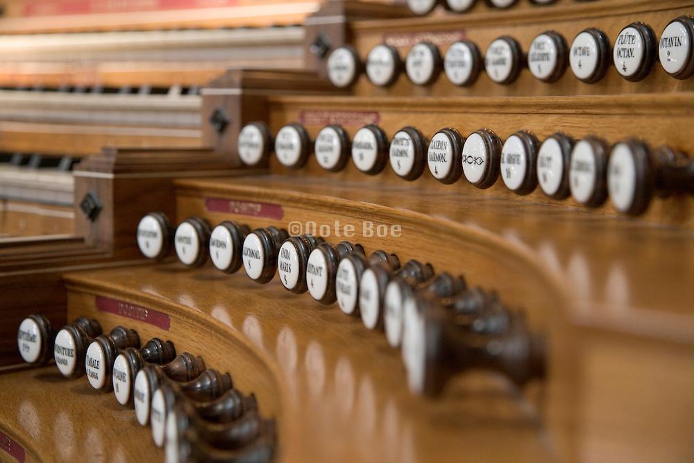 close up of an wooden organ keyboard pulls and stops