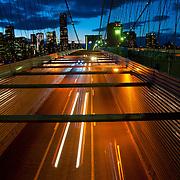 Light trails from busy traffic of Brooklyn bridge and Manhattan slyline