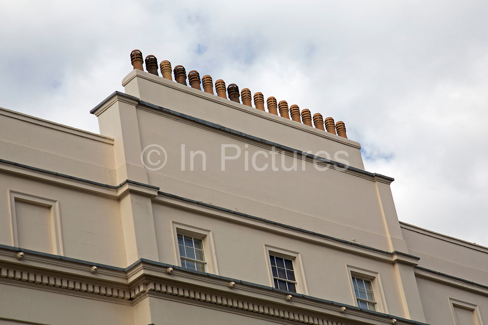 Chimney pots high above the architecture in Belgravia London, United Kingdom. Belgravia is a district in West London in the City of Westminster and the Royal Borough of Kensington and Chelsea. It is noted for its very expensive residential properties and is one of the wealthiest districts in the world. Much of it, known as the Grosvenor Estate, is still owned by a family property company, the Duke of Westminsters Grosvenor Group.