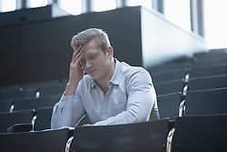 Young man sitting with tension in lecture hall with head in hands, Freiburg im Breisgau, Baden-Wuerttemberg, Germany