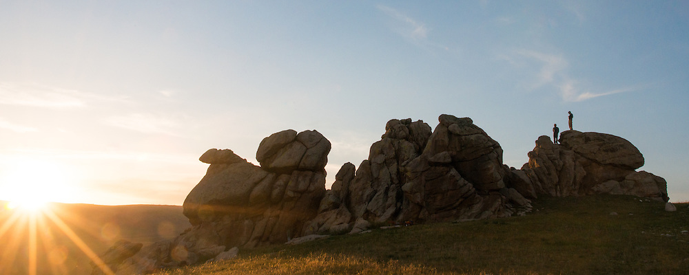 Mongolia, sunset, sculpted granite boulders and two guys in silhouette