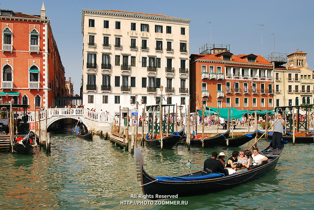 Gondolas with people in Venice canals (Italy)