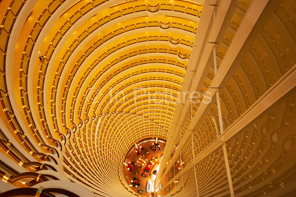 Atrium of the Grand Hyatt hotel inside the Jin Mao Building, Pudong in Shanghai, China. This view taken from the 85th floor of the Jin Mao Building looks at the top section of this amazing tower which is owned by the Hyatt hotel group. Looking down, the bottom floor in this view shows the bar area on the 55th floor. This interior has become famous as one of Shanghais tourist attractions, with many people paying to see the view from the viewing deck on the 87th floor. The symmetry and repetition of floors and balconies is breathtaking and visually overloading at the same time.
