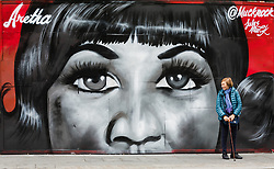 © Licensed to London News Pictures. 19/08/2018. London, UK.  A woman stands next to new street art in Shoreditch, east London, paying tribute to the singer, Aretha Franklin who has died following a battle with pancreatic cancer.  The mural has been created by artist, Jules Muck in collaboration with Global Street Art. Photo credit: Vickie Flores/LNP