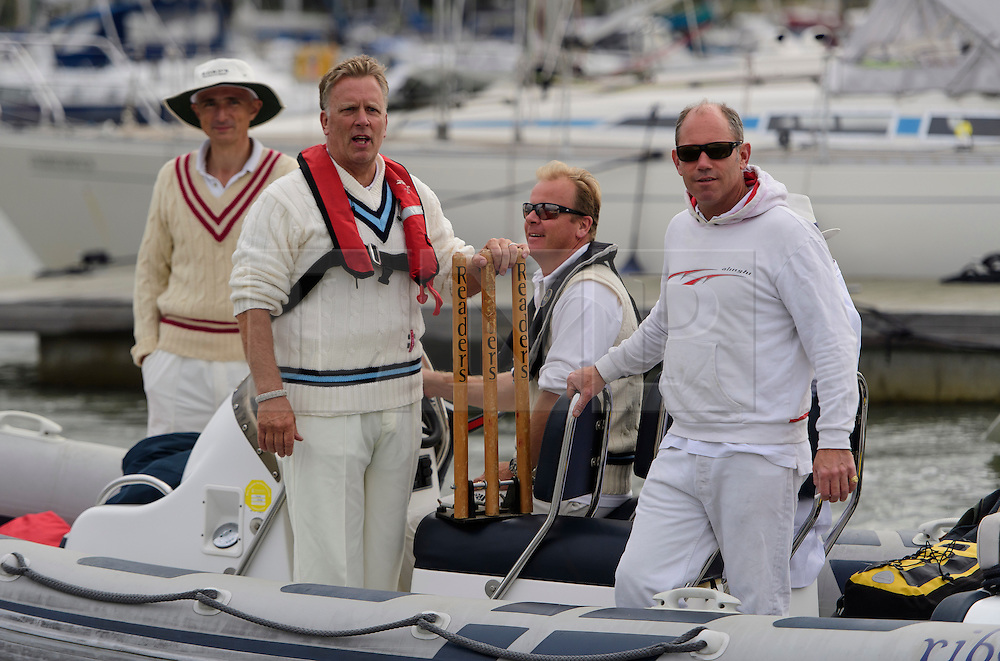 © Licensed to London News Pictures. 18/09/2016. Portsmouth, UK. Two players make their way to the match on a boat. Teams take part in the  Bramble Bank Cricket Match in the middle of The Solent strait on September 18, 2016. The annual cricket match between the Royal Southern Yacht Club and The Island Sailing Club, takes place on a sandbank which appears for 30 minutes at lowest tide. The game lasts until the tide returns. Photo credit: Ben Cawthra/LNP