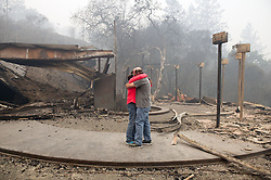 October 10, 2017 - Sacramento, California, U.S. - RHONDA READEN, left, hugs her crying partner, TIM SHIRLEY after they arrived to find their residence in the Fountaingrove area of Santa Rosa totally destroyed in Santa Rosa, Calif. Their Frank Lloyd Wright style home was burned in the Tubbs Fire which started early Monday morning. (Credit Image: © Randy Pench/Sacramento Bee via ZUMA Wire)
