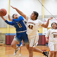 Zuni's Shelby Lalio (11) drives to the basket as Rehoboth Christian's Ashley Skeets (42) defends Friday night at Rehoboth Christian School in Rehoboth.
