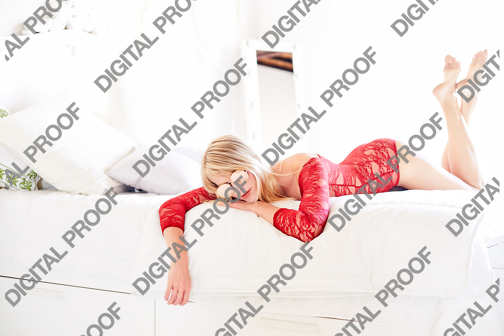 A Beautiful girl rest in bed wearing a red lace bodysuit in a interior white room.  Modern woman boudoir concept