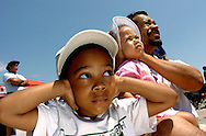 Hillsborough, Tampa, Fl. 4/9/2005--AIRSHOW 10-- From left, Josiah Russell, 4, his sister Joleah Russell, 2, and father Bobbie Russell of Valrico hold their ears  watching the F-18 demonstration while watching during the Airfest 2005 at MacDill Air Force Base Saturday, April 9, 2005. PHOTOS 12 OF IMAGES STAFF MS