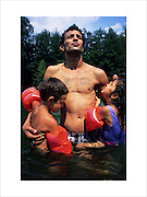 José Baptiste swimming in the river with his childen. Many Gypsies whilst called up for military service were not even given the right to vote. St.Jean du Gard, Ardeche, France 1995..Roma Gypsies left Rajasthan in India a thousand years ago, in the ninth and tenth centuries. They were pushed west by the Ottoman Muslim Empire as it moved through Persia towards the frontiers of Europe. They entered Europe in the foutrteenth century and were slaves in Romania and Moldavia until the mid 1850s. There are about 15 million Roma gypries in the world, about 12 million who live in Europe. they are Europe's largest ethnic minority. They have rich traditions and culture, their own language. They are renowned for their prowess in music and dance; they are also skilled craftsman, metal roofmakers, silver and goldsmiths. Their traveling and nomadic lifestyle which grew from a necessity to find work, and because they were often moved on from one place to the next, has given them both a liberty but also marks them as different and they are often feared by sedentary peoples, who label and scapegoat them. They are hardy survivors and live in the brunt of racism and prejudice, often marginalised, living in poverty, without proper human rights afforded to them..