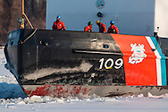 Four crew members of the United States Coast Guard cutter Sturgeon Bay stand on the deck as the icebreaker approaches a pier in the Hudson River in Hudson, New York.  Crew members wear personal flotation jackets, hard hats and eye protection while working on the deck.