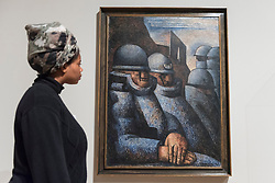 "© Licensed to London News Pictures. 04/06/2018. LONDON, UK. A gallery staff member views ""War, La Guerre"", 1925, by Marcel Gromaire at a preview of ""Aftermath:  Art in the wake of World War One"" at Tate Britain.  The exhibition marks 100 years since the end of the First World War, exploring the impact of the conflict on British, German, and French art in over 150 works from 1916 to 1932.  The show runs 5 June to 23 September 2018.  Photo credit: Stephen Chung/LNP"