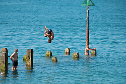 © Licensed to London News Pictures. 05/08/2018. Aberystwyth. UK. People cool off at the seaside in Aberystwyth by jumping and diving into the clear sea on a bright, warm and sunny Saturday morning  as the UK wide heatwave continues. Photo credit: Keith Morris/LNP
