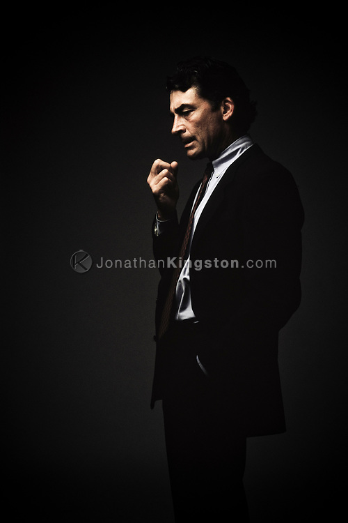 Side view of a mature man in a business suit, looking down, with his arm raised in contemplation, in Santa Barbara, California.  Three quarter length studio shot against a dark background. (releasecode: jk_mr1025) (Model Released)