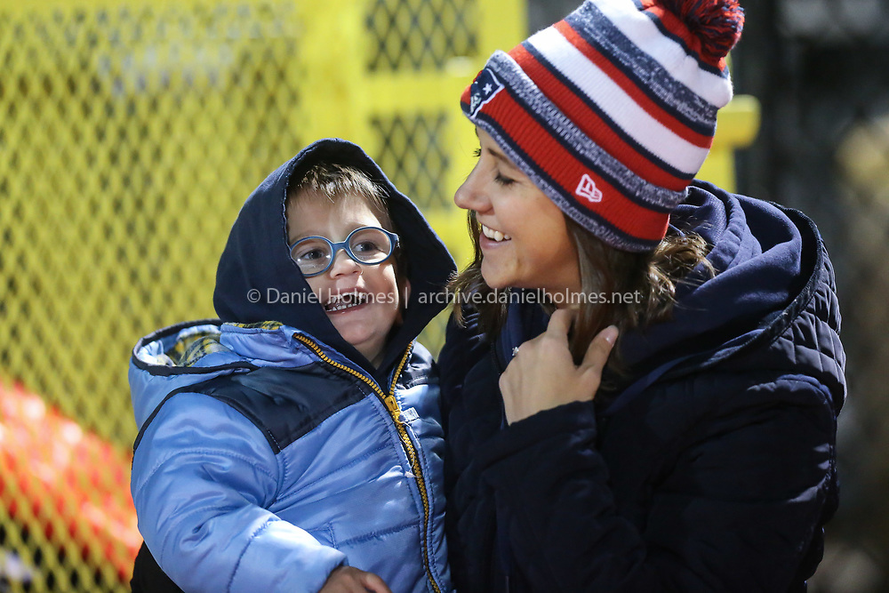 (11/1/19, FRANKLIN, MA) Jennifer Bain and her son Michael, 2, watch from the sideline during the quarterfinals of the Division 1 South playoffs against Attleboro at Franklin High School in Franklin on Friday. [Daily News and Wicked Local Photo/Dan Holmes]