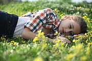 Preteen girl of 12 lies in a wildflower field
