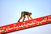 A member of the Free Syrian Army (FSA) also local resident of Marea, is seen standing on an entry welcoming sign of Marea on Wednesday, June 27, 2012. (Photo by Vudi Xhymshiti)