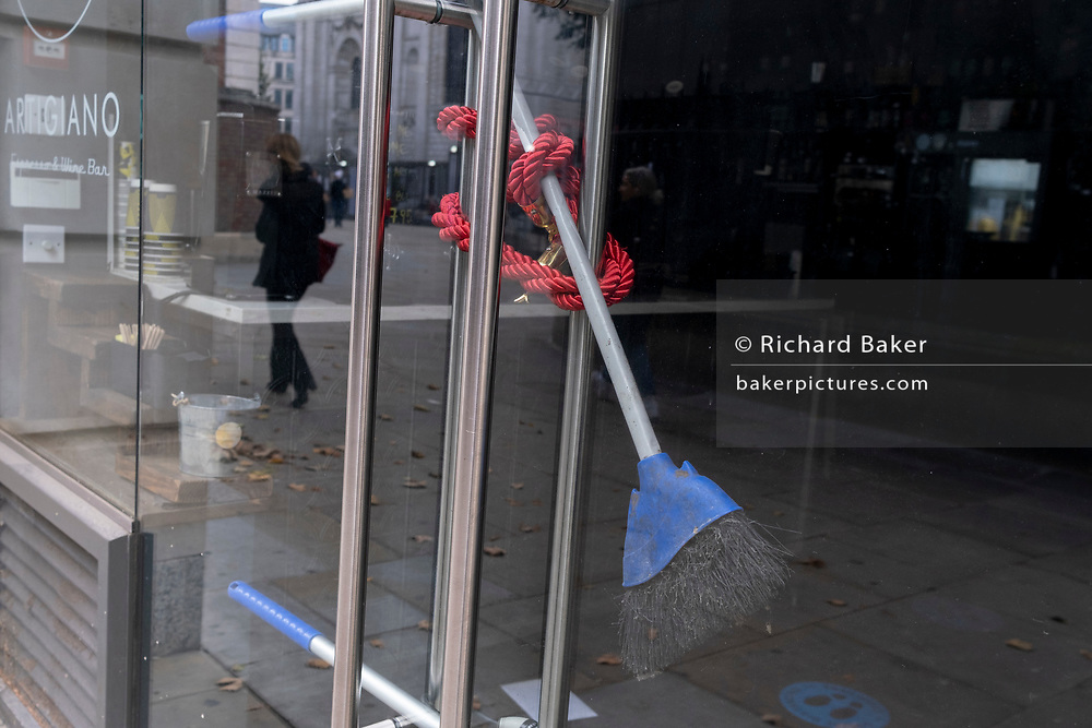 As financial district workers are still working from home, a rope cordon and a broom is wrapped around door handles of a closed wine bar during the second wave of the Coronavirus pandemic, on 26th October 2020, in London, England.