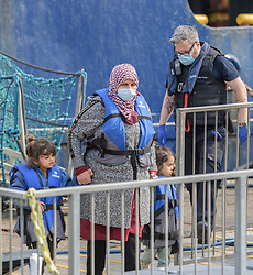 © Licensed to London News Pictures. 21/08/2021. Dover, UK. Migrant are escorted ashore by a Border Force officials at Dover Harbour in Kent, after crossing the English Channel. Photo credit: Stuart Brock/LNP