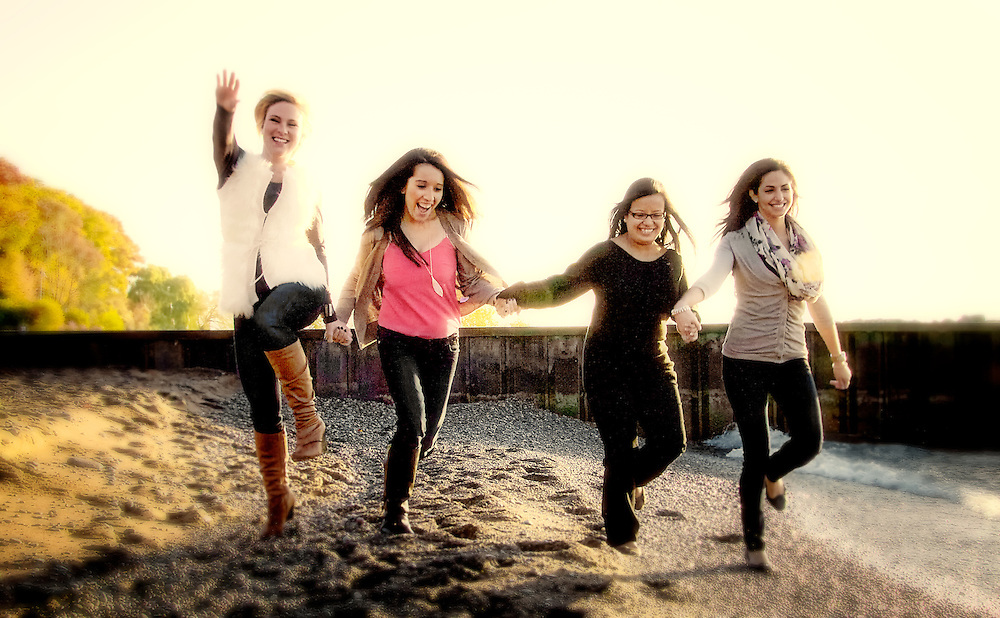 Four young adult girlfriends play along the beach waterfront