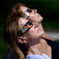 August 21, 2017 - Lexington, Kentucky, U.S. - CINDI THOMAS and ELLEN WOODWARD, both of Alexandria, Vir., joined several hundred people in Thoroughbred Park in downtown Lexington to watch the solar eclipse. (Credit Image: © Ron Garrison/Lexington Herald-Leader via ZUMA Wire)