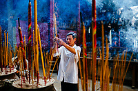 A man lights incense at a temple in Ho Chi Minh City, Vietnam.
