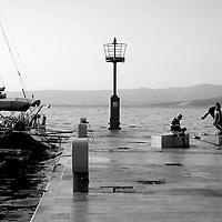Bronze fishermen statue on quay;<br />Bol Harbour,<br />Bol, Brac, Croatia.