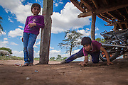 2014/11/22 – Quimili, Argentina: Gonzalo Carrizo (14), plays marbles while is sister watchs it in their house at allotment number 5 of the Guaycurú Indigenous Community. The indigenous people in the area are being threaten by soy producers that see their land as an opportunity to grow more of the crop. On the otherhand indigenous defend a sustainable agriculture and to live in harmony with the nature. (Eduardo Leal)