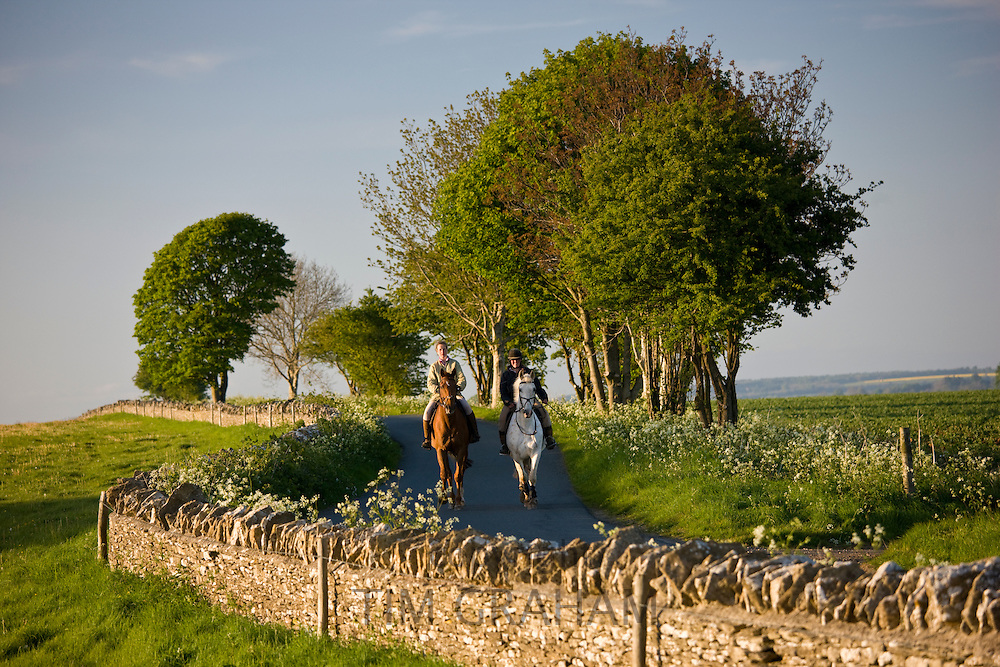 Horseriders in country lane near Cold Aston in The Cotswolds, Oxfordshire, UK