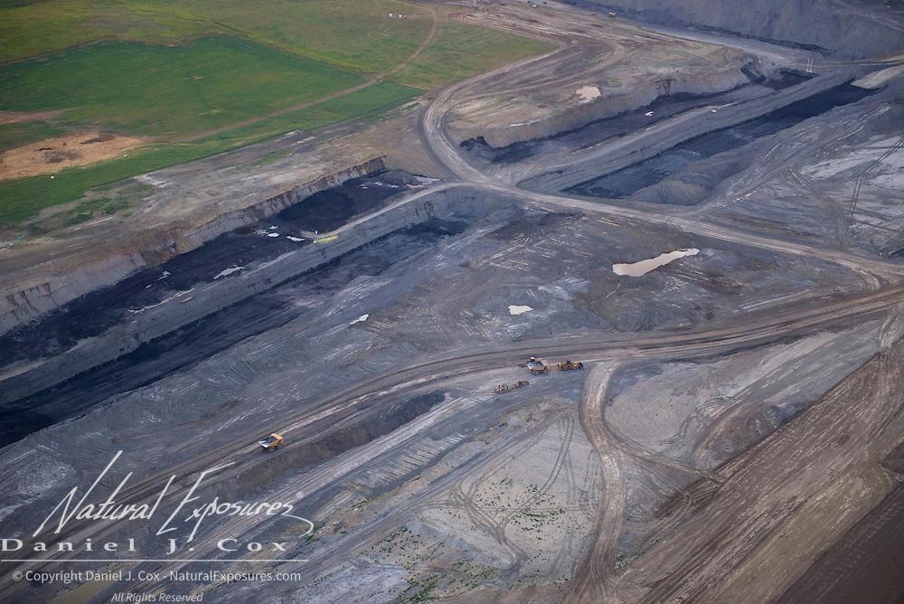 Dump trucks work an open pit coal mine also known as a surface mine in North Dakota.
