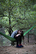 A young Vietnamese girl sleeps in a hammock in an odd position, Soc Son area, Vietnam, Southeast Asia, 2013.
