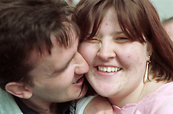Man with learning disability kissing young woman with learning disability's cheek,