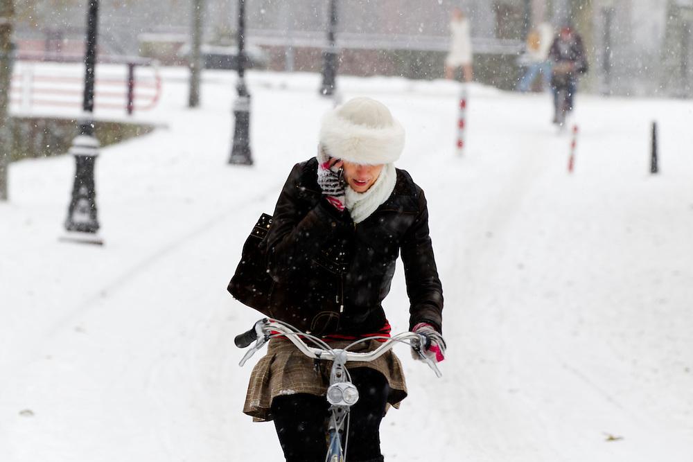 Druk bellend fietst een vrouw in de sneeuw over de Van Asch van Wijckkade in Utrecht