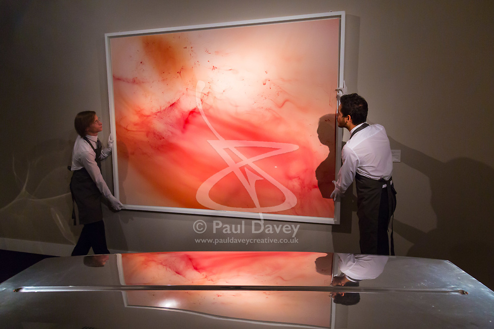 London, September 29 2017. Gallery assistants (reflected on Marc Newson's Event Horizon Table, estimated at between £100,000 - 150,000) hang Wolfgang Tillman's Urgency XVI, estimated to fetch between £300,000 - 500,000 at Christie's Masterpieces of Design and Photography sale in London on 3rd October 2017. © Paul Davey