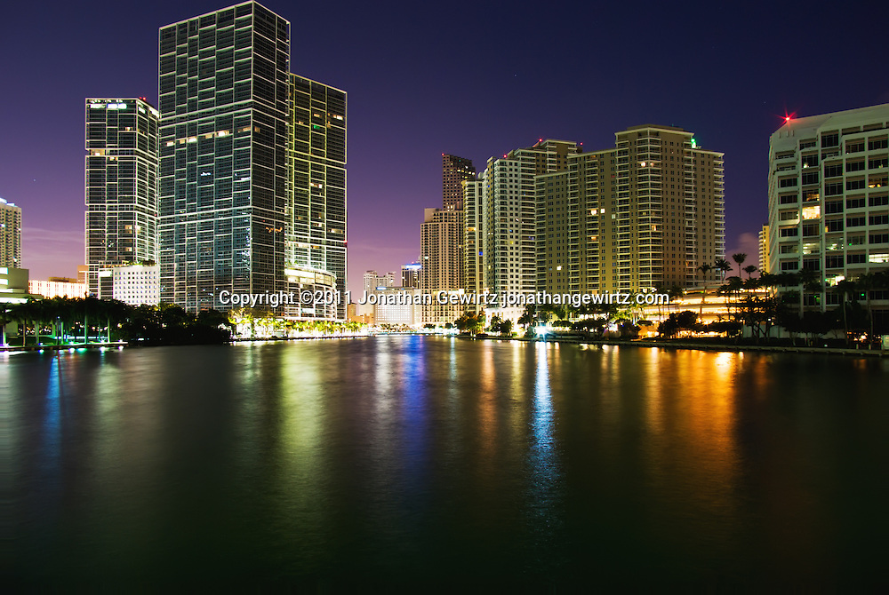 Brightly illuminated condos, hotels and office buildings on Biscayne Bay between Downtown Miami and Brickell Key at night. WATERMARKS WILL NOT APPEAR ON PRINTS OR LICENSED IMAGES.