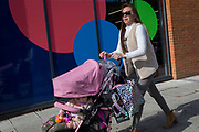 A mother pushes her child's buggy past the circles of a local gym, on 2nd October 2019, in Sutton, London, England