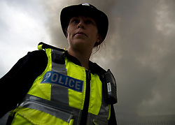 © Licensed to London News Pictures. 01/09/2013. Leyland, UK. A police officer marshals the crowd. The scene at Leyland St Mary's Catholic Technology College in Leyland, Lancashire as it was devastated by the blaze at 4pm yesterday (1st September 2013), which saw 100ft flames - and was tackled by 125 firefighters and 20 engines. Photo credit : Pat Tack/LNP